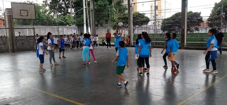 Crianças estão jogando vôlei em quadra usando coletes na cor azul claro durante aula de Educação Física, disciplina é valorizada pelo conceito de escola ativa.