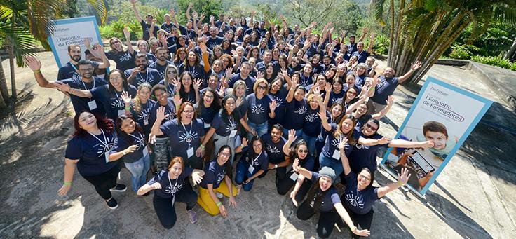 Participantes do 1º Encontro de Formadores do Aula Digital posam para foto em grupo com as mãos levantadas