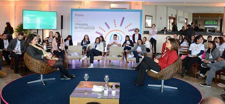 Sentada à direita, Mila Gonçalves, gerente-sênior de Programas Sociais da Fundação Telefônica Vivo, participa de painel e conversa com Caroline Tavares, do movimento Profissão Docente, sentada à esquerda da plenária. Ao fundo, os participantes estão sentados em volta do palco.