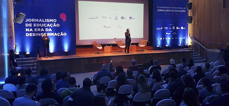 Jornalista Antônio Góis está vestido de terno e falando ao microfone no palco do Jeduca 2019, durante a abertura do congresso que discute relação entre comunicação e educação.