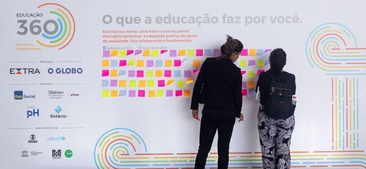 """Imagem mostra pessoas colando post-its coloridos em um banner onde se lê """"O que a Educação faz por você"""". Ao lado se vê o nome do evento: Educação 360 e os logotipos de parceiros e patrocinadores."""