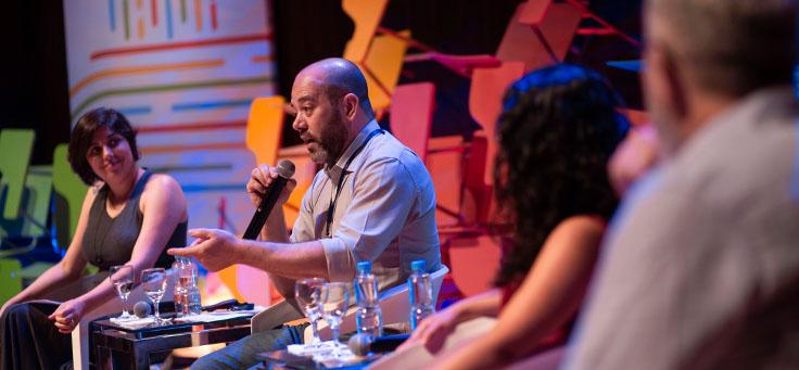 Americo Mattar, diretor-presidente da Fundação Telefônica, fala durante evento, enquanto é observado por outros integrantes da mesa.
