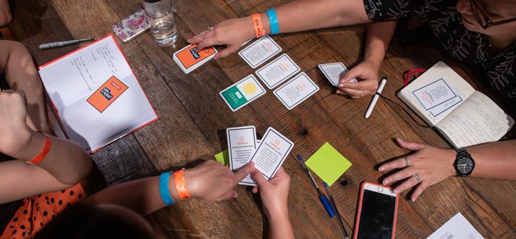 """Integrantes do evento participam do """"Jogo Vida e Ação"""". É possível ver anotações e post-its na mesa"""