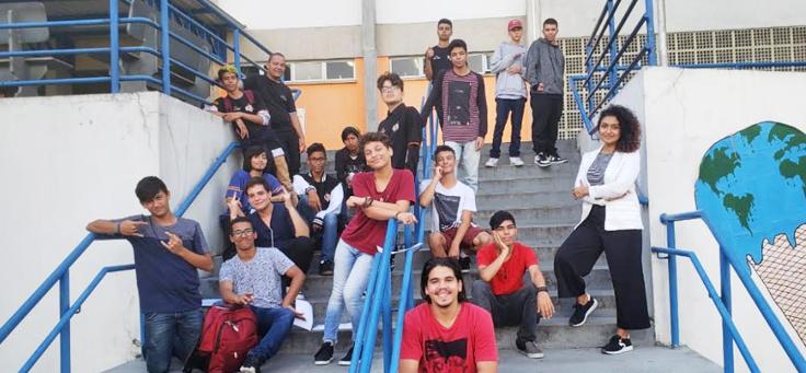 Imagem mostra grupo de alunos posando para foto, sentados em uma escada dentro da escola.