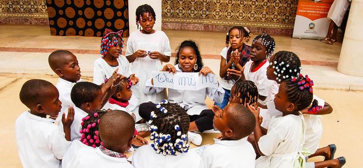 Na imagem, professora está rodeada de alunos e segurando cartaz em que se lê algumas sílabas. Em Angola programa usa atividades lúdicas para inovar ensino-aprendizagem.