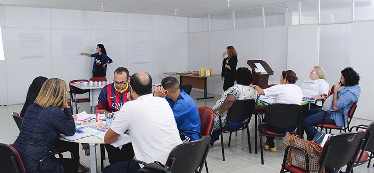 Imagem mostra professores sentados em carteiras dentro de uma sala e dois formadores do programa em pé