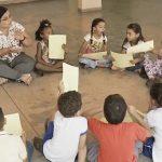 Imagem mostra a professora Elenice sentanda no chão com seus alunos em uma roda.