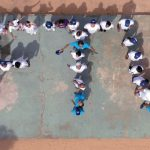 Imagem mostra plano área de um grupo de pessoas posicionadas no solo formando o símbolo FTV