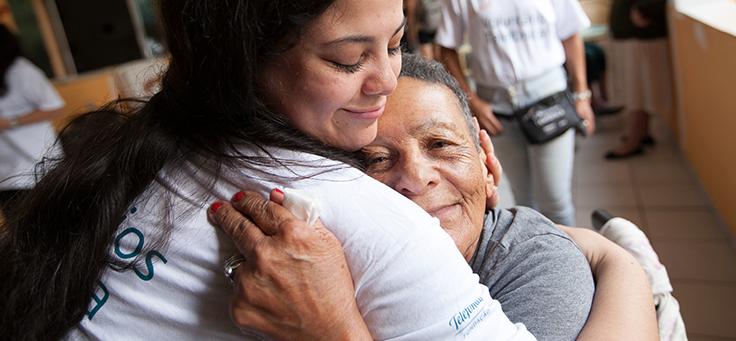 Imagem mostra voluntária abraçando uma senhora durante o Dia dos Voluntários