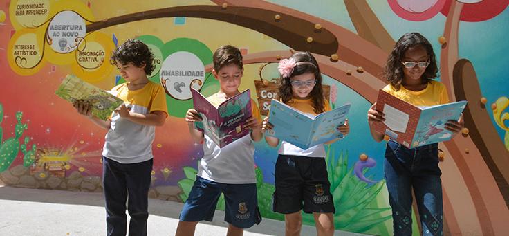 Quatro crianças estão segurando livros em frente a um muro com desenhos coloridos em escola de Sobral (CE), que tem rede de ensino modelo em alfabetização de qualidade.