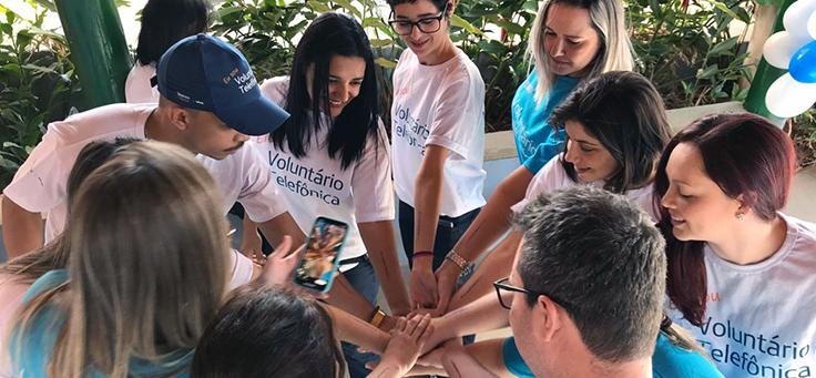 Imagem mostra voluntários formando uma roda em pé, juntando as mãos