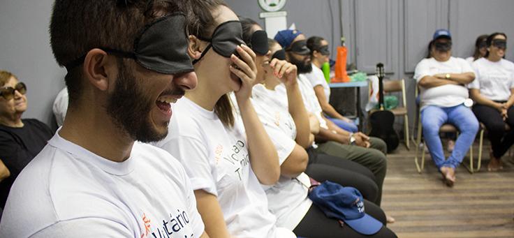 Imagem mostra pessoas sentadas com os olhos vendados