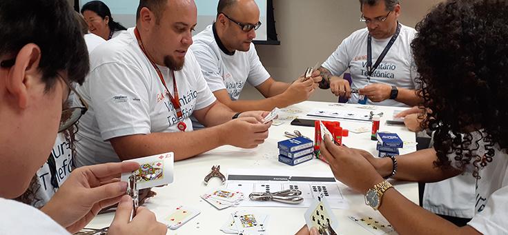 Imagem mostra voluntários produzindo baralho adaptado para defiientes
