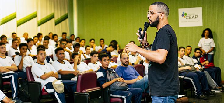 Imagem mostra um homem de pé em um auditório falando no microfone para um grupo de estudantes