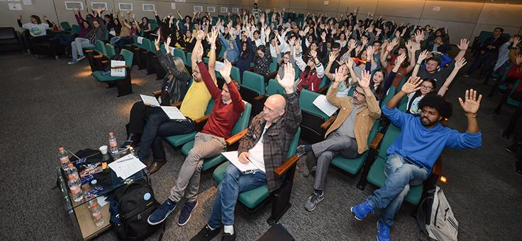 Plateia do Demoday levanta os braços e aplaude durante apresentações.