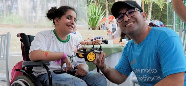Imagem mostra voluntaria ao lado de uma das crianças atendidas pela associação, que está em uma cadeira de rodas