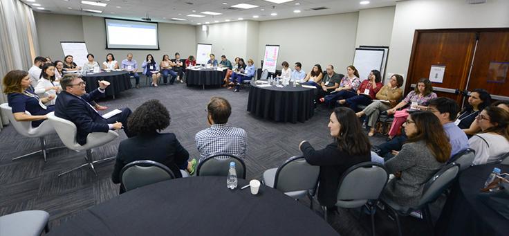 Integrantes da rede do Escola Digital estão sentados em roda conversando com especialistas, em meio a charts e um telão, durante o encontro ocorrido em São Paulo.
