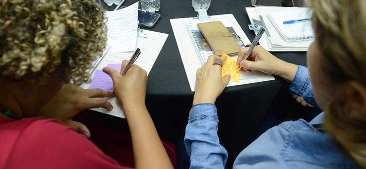 Duas integrantes da rede do Escola Digital aparecem de costas, escrevendo em post its durante encontro ocorrido em São Paulo.