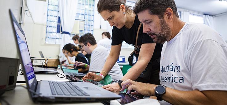Imagem mostra voluntários em um sala de aula com notebooks