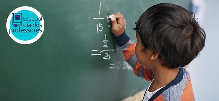 Imagem mostra menino escrevendo números com giz em uma lousa durante uma aula de matemática.