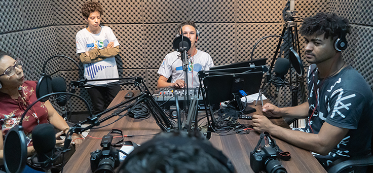 Imagem mostra pessoas dentro de um estúdio de gravação