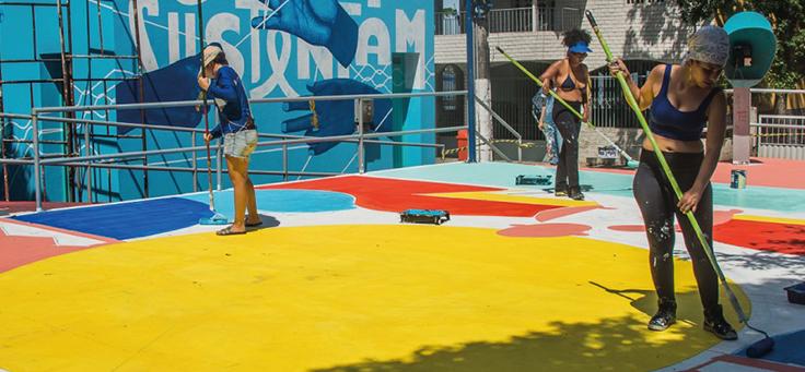 Equipe da Cidade Quintal, uma das iniciativas voluntárias da lista, está pintando uma quadra na cidade de Vitória.