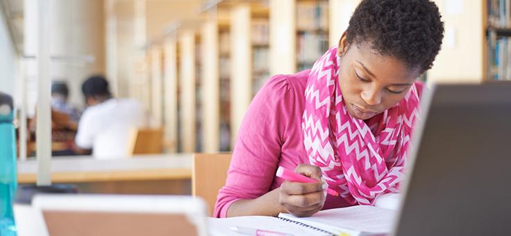 Aluna de curso de educação a distância está estudando em frente a tela de computador. Ela tem cabelos crespos e curtos e usa lenço rosa estampado no pescoço.