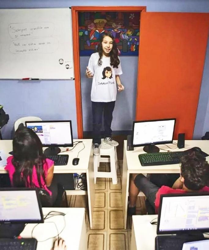 Imagem mostra Teteus Bionic em pé na frente dasala de aula, com crianças sentadas em mesas com computadores.