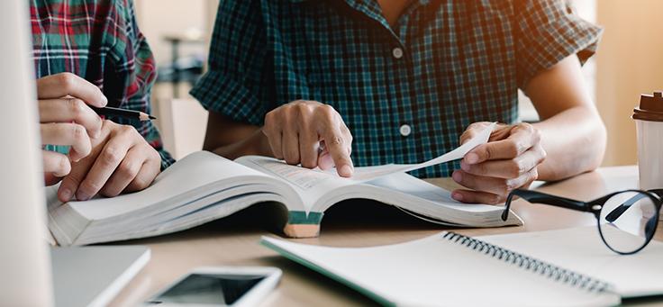 Na imagem duas pessoas estão sentadas lado a lado procurando informações em um livro e há um óculos e um caderno sobre a mesa. Conheça e ressignifique 11 termos sobre voluntariado.
