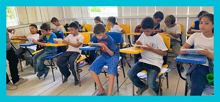 Imagem mostra alunos dentro de uma sala de aula manuseando os tablets que fazem parte do projeto Aula Digital
