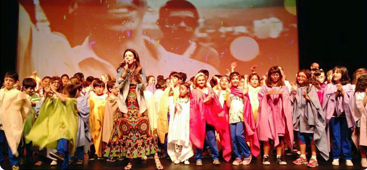 Imagem mostra um grupo de crianças em cima de um palco com roupas customizadas e um telão projetando uma imagem ao fundo. Na frente delas está uma mulher segurando um microfone.