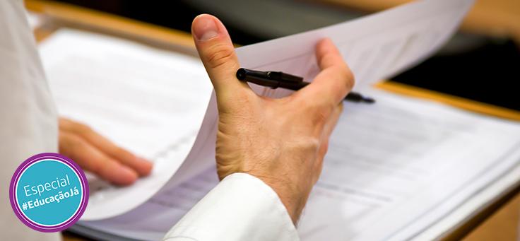 Imagem mostra uma mão em destaque mexendo em uma folha de papel e segurando uma caneta