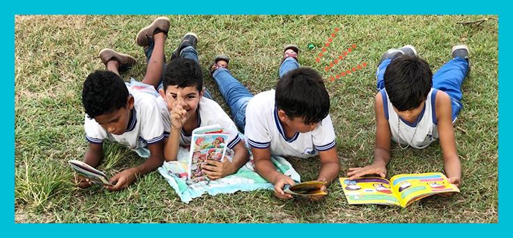 Quatro meninos estão deitados em gramado lendo livros em atividade do projeto de estímulo à leitura piquenique literário, criado por meio do Aula Digital.