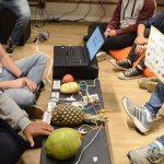 Voluntário está segurando placa que associa frutas conectadas a computador a sons em atividade que ensina programação a pessoas com deficiência intelectual.