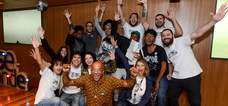 Na imagem, grupo de pessoas que participou do Demoday posam para foto em grupo em cima de um palco