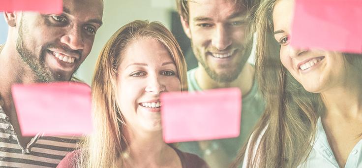A imagem mostra quatro pessoas sorrindo enquanto olham para um quadro transparente em que se vê post-its colados.