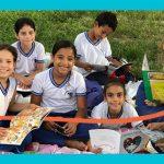Crianças estão agrupadas em meio a gramado segurando livros e sorrindo, ao lado de educadora que conduz o projeto de estímulo à leitura Piquenique Literário.