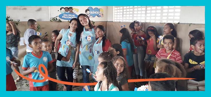 Educadoras estão sorrindo em meio a crianças durante atividade do Chá Literário, projeto de estímulo à leitura criado por meio do Aula Digital.