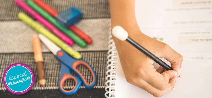 Imagem mostra uma mão em destaque escrevendoem um papel de lápis