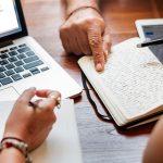 Imagem mostra um notebook, um caderno e um tablet em cima de uma mesa, com o destaque de algumas mãos segurando canetas e apontando para a folha de caderno