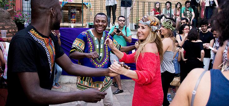 Pessoas sorriam e dançam ao lado de refugiados
