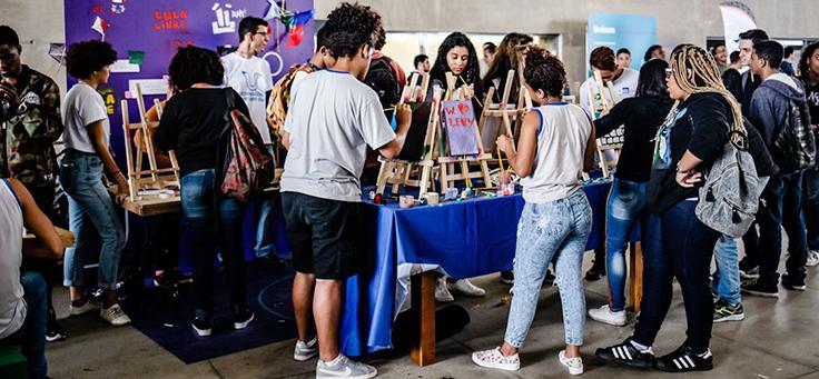 Pessoas participam de ação voluntária com cavaletes de pintura sobre uma mesa.
