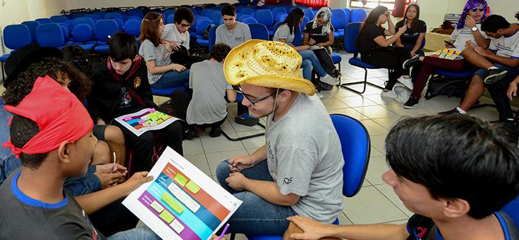 Imagem mostra pessoas realizando uma atividade em grupo dentro de uma sala