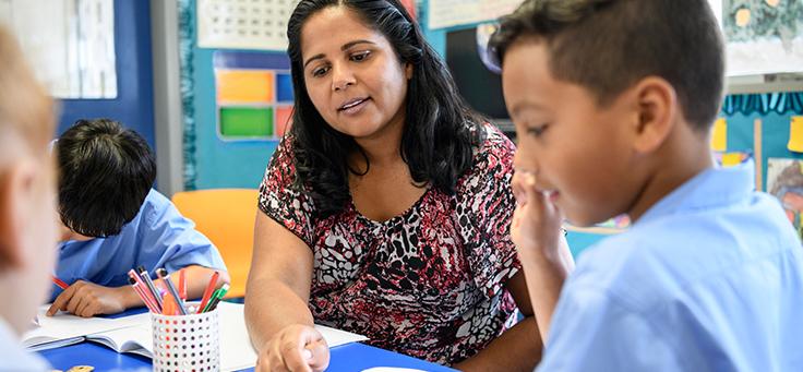 Imagemde uma professora com um aluno sentados