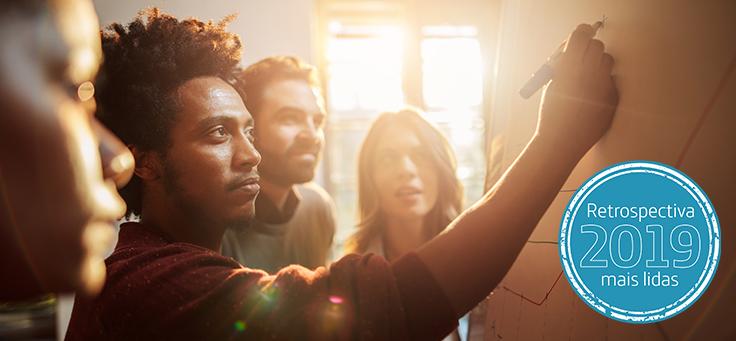Imagem mostra quatros pessoas olhando para um quadro branco com um gráfico desenhado. Umdeles segura uma caneta e desenha no mesmo quadro.