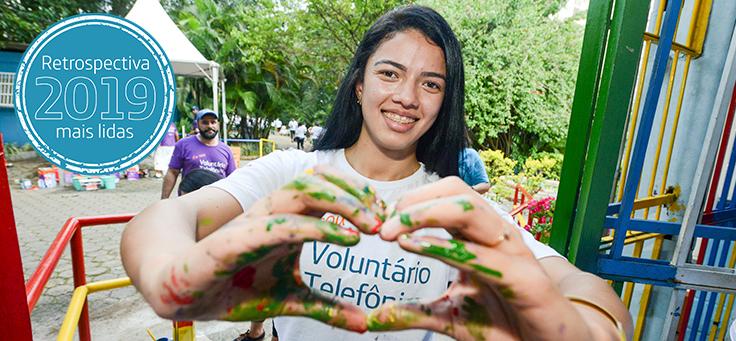 Imagem mostra colaborada do Grupo Telefônica Vivo sorrindo e fazendo um coração com as mãos, que estão sujas de tinta. Ela veste uma camiseta do Programa de Voluntariado da Fundação Telefônica Vivo