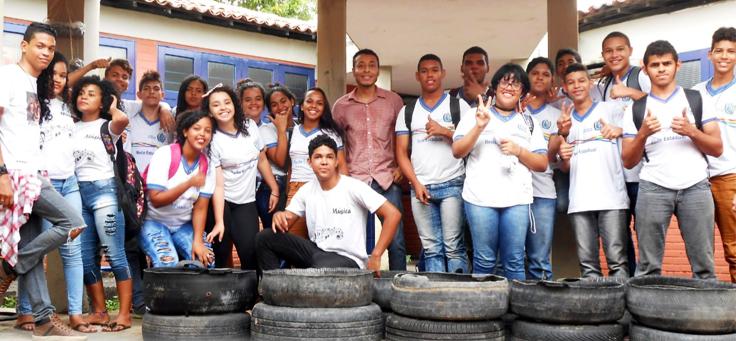 Na imagem, um grupo de alunos de uniforme posa para foto em grupo junto ao professor deles