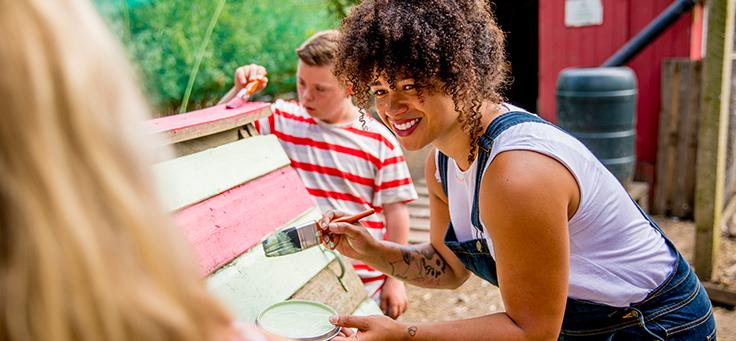Imagem mostra jovem segurando um pincel em frente a um banco de madeira. Ao fundo, um jovem está pintando o mesmo banco