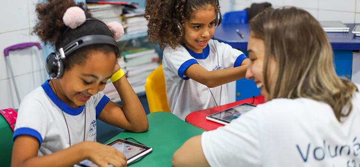 Imagem de duas crianças, de uniforme escolar, sentadas e utilizando fones de ouvido. Na frente de uma deles, uma mulher com uma camiseta de voluntária sorri.
