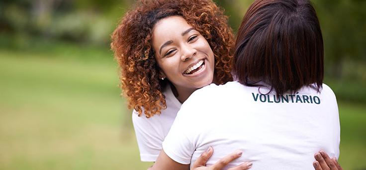 A imagem mostra duas mulheres que participam de programa de voluntariado empresarial estão se abraçando, sendo que é possível ver as costas de uma delas e o rosto sorridente da outra.